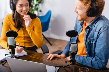 Selective focus of asian radio host talking to colleague in radio studio stock vector