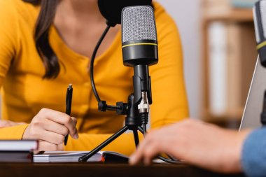 Cropped view of broadcaster holding pen during interview with man in radio studio stock vector