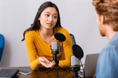 Selective focus of brunette asian radio host gesturing while interviewing man in studio stock vector