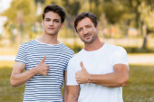 father and teenager son in t-shirts showing thumbs up in park