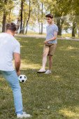 selective focus of teenager son playing football with father