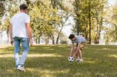 selektivní zaměření dospívajícího syna dotýkajícího se fotbalu poblíž otce