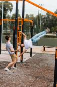 teenager syn ukazuje rukou při pohledu na sportovní otec cvičení na horizontální tyče