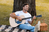 Photo man sitting on blanket under tree and playing acoustic guitar