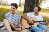 selective focus of teenager boy holding smartphone near father playing acoustic guitar