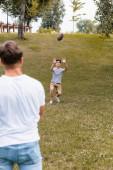 selektivní zaměření teenager syn lov rugby míč v blízkosti otce v parku