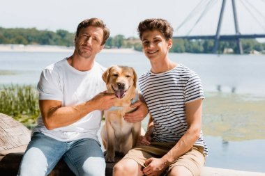 Father and son looking at camera while sitting near lake with golden retriever stock vector