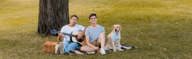 panoramic crop of teenager boy and father sitting on blanket near golden retriever under tree trunk