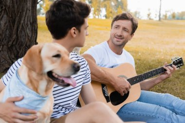 selective focus of man playing acoustic guitar near teenager son and golden retriever in park