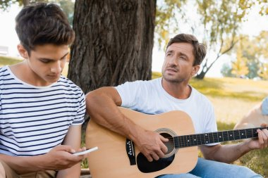 selective focus of father playing acoustic guitar near teenager son using smartphone
