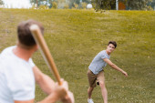 Photo selective focus of teenager boy throwing ball while playing baseball with father