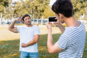selective focus of strong father posing while teenager boy taking photo and holding smartphone in park
