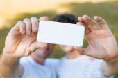 szelektív fókusz okostelefon kezében apa és tinédzser fiú selfie