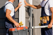 Cropped view of builders with toolbox and tool belt standing near facade of building outdoors
