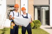 Bauarbeiter mit Blaupause schauen auf Rasen neben Gebäude in die Kamera