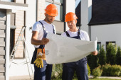 Workmen in overalls and helmets looking at blueprint near building