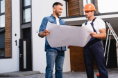 Workman in helmet holding blueprint near man and building outdoors
