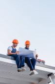 Niedrige Winkelaufnahme von Arbeitern mit Blaupause, während sie in der Nähe des Werkzeugkastens auf dem Dach des Gebäudes sitzen
