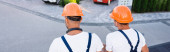 Photo Panoramic shot of builders sitting on roof of building on urban street