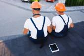 Pohled zezadu na stavitele sedící poblíž digitálního tabletu na střeše budovy