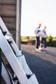 Selektivní zaměření žebříku a stavitelů pracujících na střeše domu v pozadí