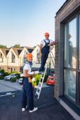Stavbaři s plánem a žebříkem při pohledu do kamery na střeše budovy