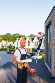 Selective focus of builder with toolbox and blueprint standing on roof of building