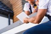 Oříznutý pohled na stavitele pomocí digitálního tabletu na střeše domu