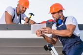 Opraváři v montérkách a přilbách pomocí digitálního tabletu na střeše domu