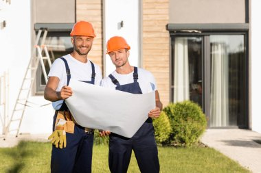 Builders with blueprint looking at camera on lawn near building stock vector