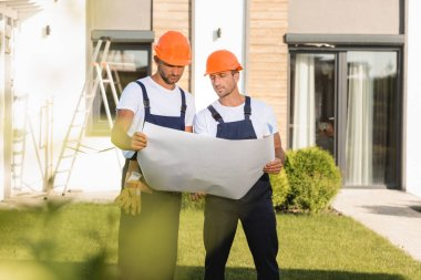 Selective focus of builders in overalls and hardhats looking at blueprint near building stock vector