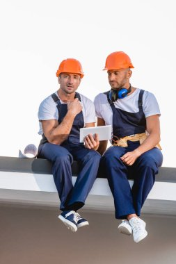 Builders using digital tablet while sitting on roof of building isolated on white stock vector