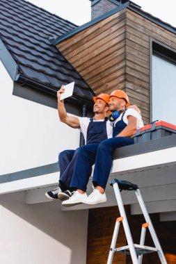 Builders taking selfie on digital tablet while sitting on roof of building stock vector