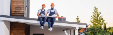 Panoramic shot of builders in uniform holding blueprint near toolbox on roof of building stock vector