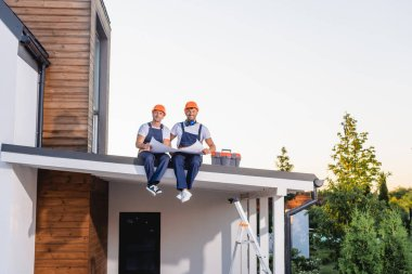 Builders looking at camera while holding blueprint near toolbox on roof of building stock vector