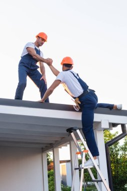 Builder helping to colleague on ladder near roof of building stock vector