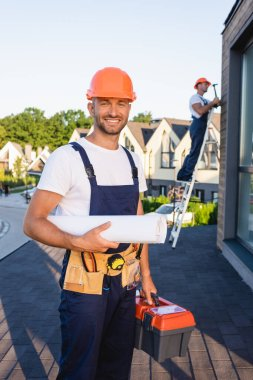 Selective focus of builder in tool belt holding blueprint and toolbox near colleague on roof stock vector