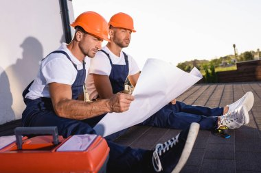 Selective focus of builders with blueprint sitting near toolbox while working on roof of house stock vector