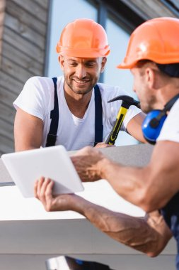 Selective focus of builder holding hammer near colleague with digital tablet on roof of building stock vector