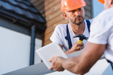 Selective focus of builder with hammer looking at colleague with digital tablet on roof of building stock vector