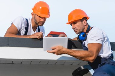 Selective focus of handymen in workwear using digital tablet while working on roof of building stock vector
