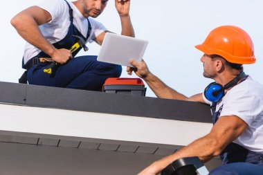 Selective focus of builder showing digital tablet to colleague with hammer on roof of building stock vector