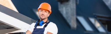 Panoramic shot of builder in hardhat looking at camera near roof of building stock vector