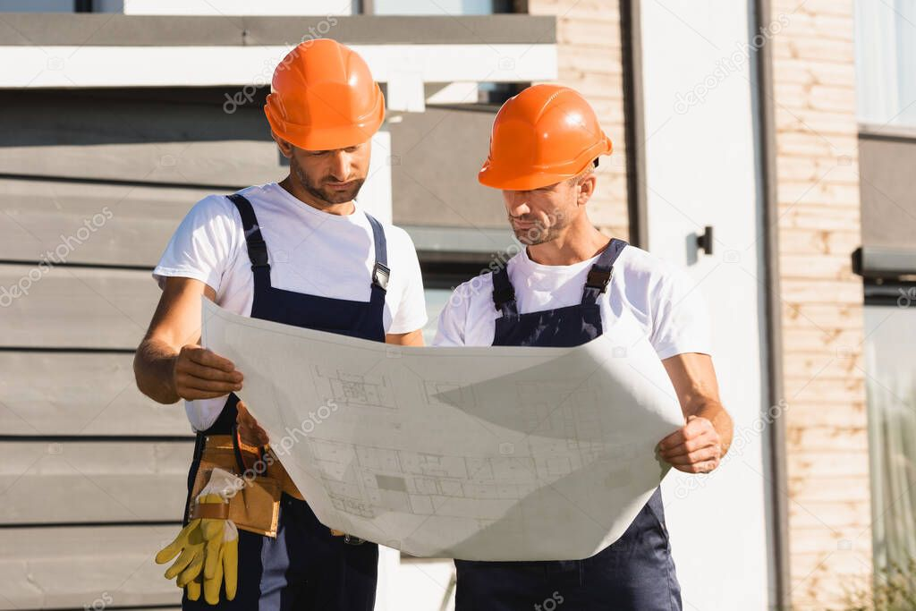 Builders holding blueprint while working near building stock vector