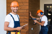 Selective focus of builder holding digital tablet while colleague using electric screwdriver near facade of building