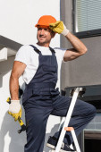 Builder in overalls holding hammer while touching hardhat on ladder near house