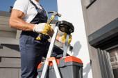 Oříznutý pohled na dělníka s kladivem stojícím na žebříku s bednou s nářadím poblíž budovy