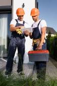 Photo Selective focus of builders with tool belt and toolbox using digital tablet on urban street