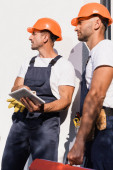 Photo Selective focus of handymen with digital tablet and toolbox standing near facade of building