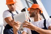 Selektiver Fokus des Bauunternehmers mit digitalem Tablet in der Nähe des Kollegen auf der Leiter in der Nähe des Gebäudes